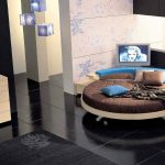 lovable brown and blue round bed idea with tv screen and black flooring in creamy painted wall with black accent