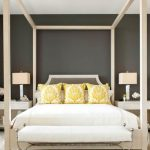 lovable white bedding with yellow pillows and white bench and metal canopy and simple headboard