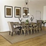lovely and formal dining room design with gray wing chairs and wooden chair and wooden floor and chandeloer and gray are rug