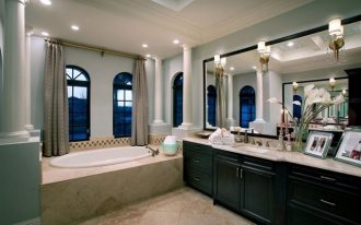 luxurious bathroom design in american home designwith concrete recessed bathtub and black vanity with framed wall mirror and wall lamps