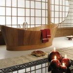 luxurious bathroom design with open plan idea and stunning wooden bathtub with red towel and curved faucet with glossy flooring and candelabrum