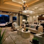 luxurious classic american house with stunning formal living room with double round coffee table and gray wing chair and chandelier and table lamps