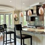 luxurious classic interior design of kitchen and dining room with marble top and unique coccoon pendants and black scandinavian stools