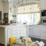 luxurious classic kitchen desgn with large island and white cabinert and tile gray flooring and dog pillow