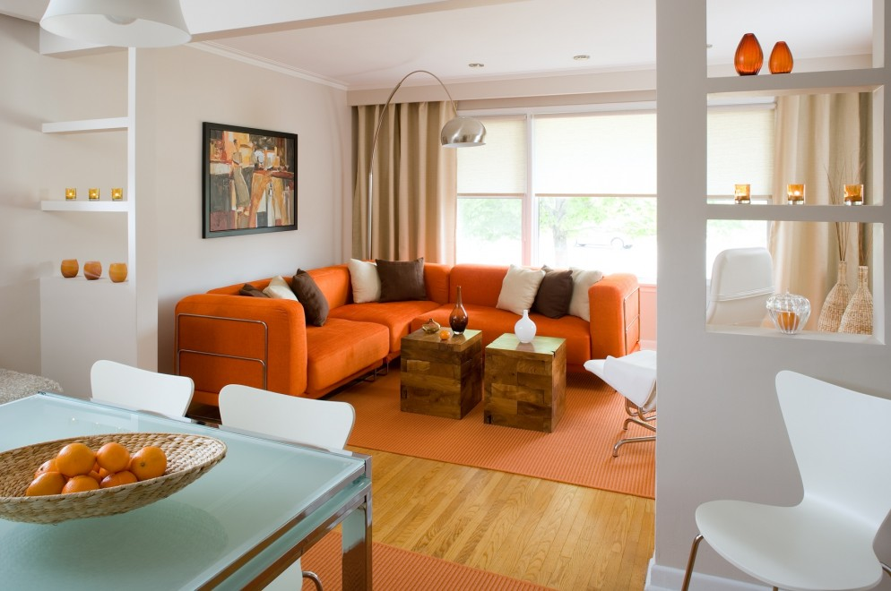 luxurious living room design with sectional orange sofa and brown white throw pillows and wooden floor - Orange Living Room Design