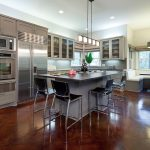 luxurious open kitchen design idea with gray cabinet and island and black stools and painted concrete flooring