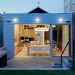luxurious small house design with open plan adn extended living space and glass door and deck facade and wall lighting