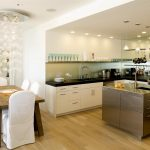 Luxurious White Open Kitchen Design Idea With White Cabinet And Stainless Steel Island And Wooden Dining Table And White Chairs And Wooden Floor