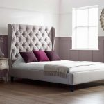 Luxury Scarlett Tall Upholstered Bed With Luxurious Tufted Headboard And Wooden Floor Plus Nightstand Table And Round Mirror On Wall