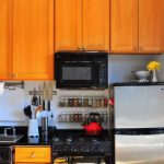 magnetic-kitchen-knife-mounted-on-the-wall-under-wooden-finishing-cabinets-near-other-kitchen-utensils-and-sink