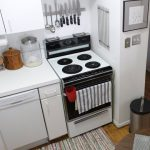 magnetic-strip-for-knives-and-other-metal-kitchen-utensils-mounted-on-the-wall-under-the-white-cabinet-and-above-the-stove-r-oven-in-white-color-theme