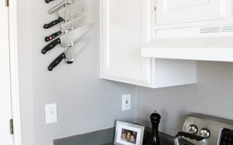 magnetic-strip-for-knives-vertically-mounted-on-the-white-wall-near-the-door-and-near-white-cabinets-also-7-various-knives-on-the-magnetic-strip