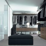 master walk in closet design with black pouff and wooden dresser and glass sliding door and white flooring