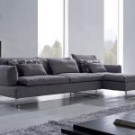 modern living room design with gray long sectional sofa design with furry area rug and black coffee table and dresser