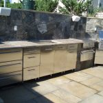 modern stainless steel outdoor kitchen cbainet idea with wooden top aside stone fenece with rustic flooring design