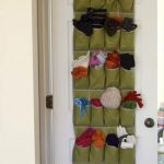 Over The Door Shoe Holder With Green Army Color Use For Storing And Organizing And Stowing Hats And Gloves Hang On White Door