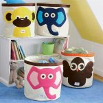 pink-and-blue-elephant-also-brown-owl-and-yellow-monkey-storage-bins-by-3-sprouts-on-blue-carpet-near-white-bookshelf-with-dolls-and-toys