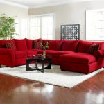 red  microfiber sectional sofa with chaise and throw pillows a glass top coffee table with unique wood base white area rug