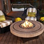 round fire pit table made of solid and unfinished wooden table a pair of black rattan chairs with cushions and glossy green accent pillows