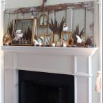rustic mantel decor adorned with small framed mirror and feather plus decorative owl ornament plus pine cone for affectionate room