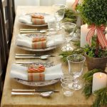 rustic wooden dining table with christmas centerpiece design and topiary and pink ribbon and candelabrum