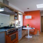 simple and elegant kitchen design with orange accent and white dominant tone with glass window and wooden flooring