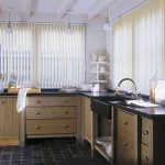 simple and elegant kitchen design with vertical white blind and rustic wooden cbainetry and black tile flooring