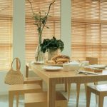 simple and exotic rattan rolled blind in he kitchen with a set of beige dining table with indoor plant