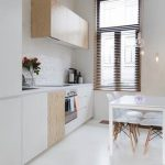 simple and modern kitchen design with white painted wall and white cbainetry and glass window with traditional blind and white dining set