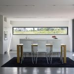 simple kitchen interior design with black area rug and wooden table and white chairs and island and sliding glass door