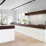 sleek kitchen design in white color with brown wooden accent on the wall and top and white cabinet and wooden flooring and glass window and door