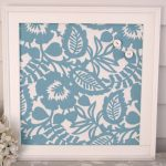 small decorative magnetic board with patterned background and white wooden frame for home accessories
