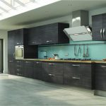 spacious black kitchen design with wooden cabinet and turquoise accent and white dining table and black chairs and skylight