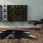 spacious interior design with black brown reclining leather chair and unique area rug and wooden floor and wine rack on the wall