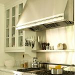 stainless-kitchen-with-magnetic-strip-for-knives-mounted-on-the-side-of-white-cabinet-and-above-the-stove