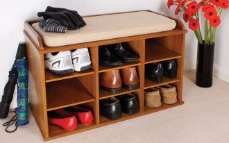 stunning furnished wooden shoe storage in the entry with pigeon hole and potted plants