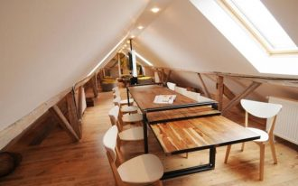 stunning loft dining room design with wooden dining table with wooden chairs beneath white sloping ceiling with skylight