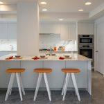 stunning modern whit kitchen design with large white island bar and orange wooden scandinavian stools idea on gray concrete painted floor