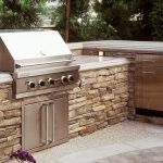 stunning rustic brick outdoor kitchen cabinet with white marble countertop and paved flooring aside green garden