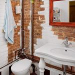 stunning small bathroom in the loft with scratched wall accent decoration with simple freestanding vanity and toilet seat and wall lamps and framed mirror