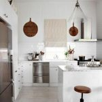 stunning white kicthen design with various pendants and white island and wooden cabinetry and creamy blind