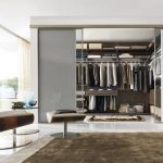 stunning white open plan walk in wardrobe design with gray storage and brown reclining sofa with brown furry rug and open plan and white shade floor lamp