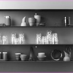 stylish gray painted wall with stainless steel floating shelf for table ware and wine glasses