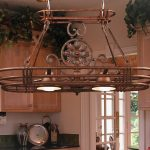 stylish pot rack with lights made of metal and two lamps on it plus wooden counters