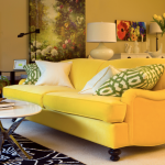stylish yellow couch design with patterned gray yellow cushion and oval white coffee table and black aptterned area rug