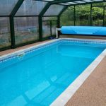 super slim swimming pool design with transoarent canopy with brown patio deck