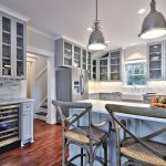 traditional kitchen decorating ideas with wooden kitchen cabinets plus beveled arabesque tile for backsplash and kitchen island with rustic bar stool and wooden floor