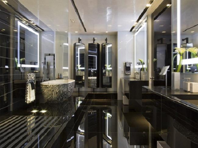 trend bathroom design with black glossy flooring and sparkling wall and white bathtub and luxurious vanity and modern lighting