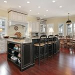 two-tier-Kitchen-Island-with-Side-Storage-in-black-with-light-granite-countertops-on-warm-hardwood-flooring-and-white-cabinetry-with-three-tall-pub-chairs