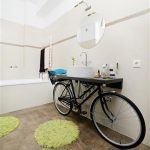 unique apartment interior bathroom idea with bicycle vanity in black color and round wall mirror and modern lighting